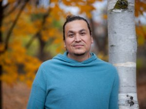 A portrait of Philip Macho Commonda, wearing a blue shirt, leaning against a birch tree with fall foliage in the background